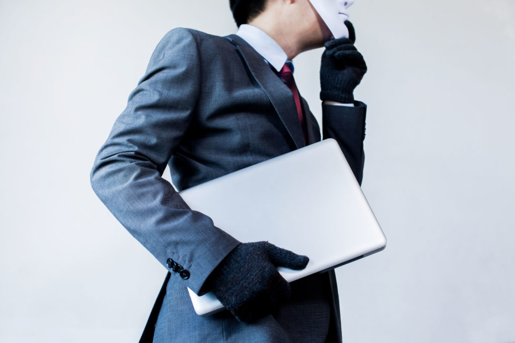 Business man holding laptop while wearing white mask