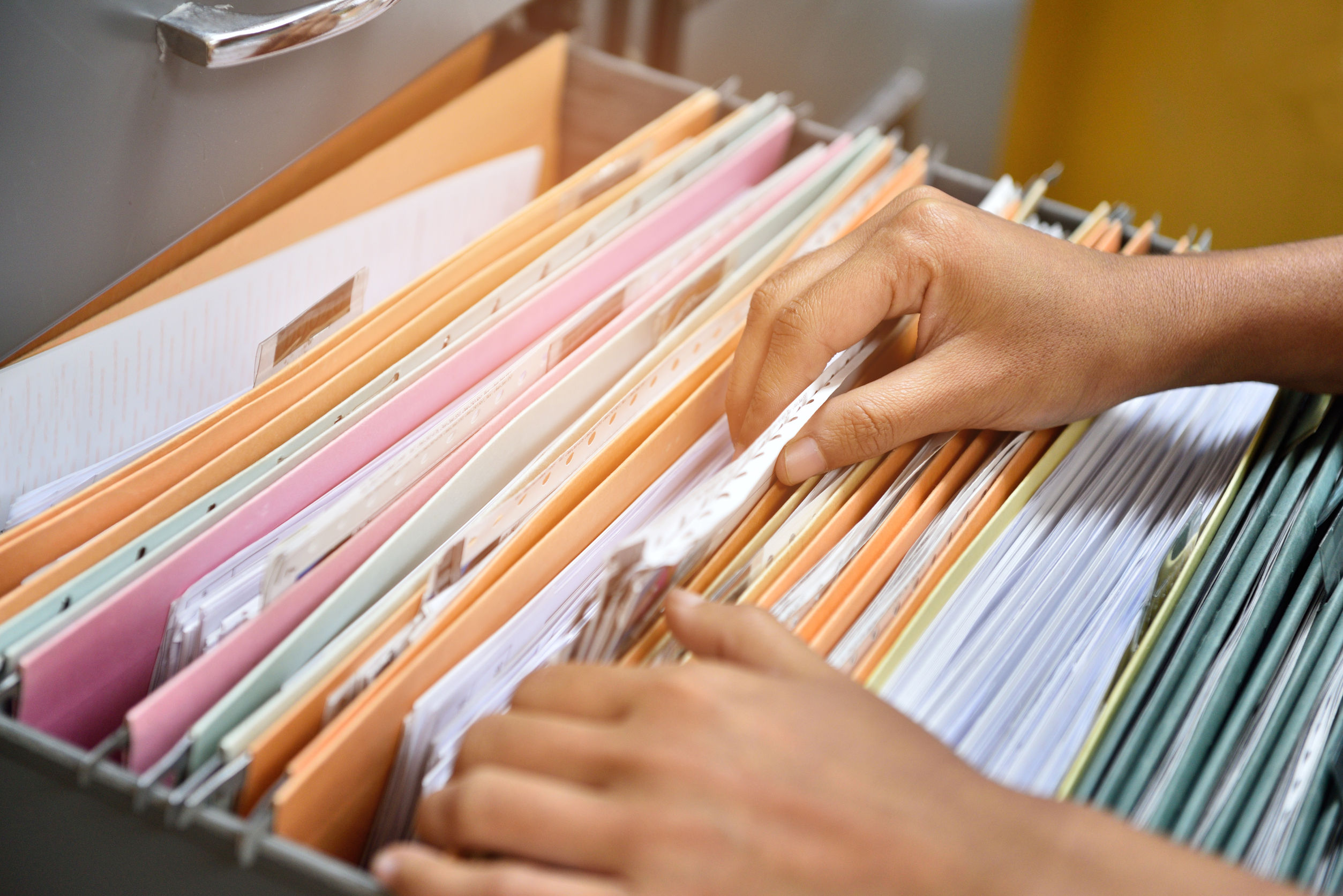 Hands searching through file cabinet and folders