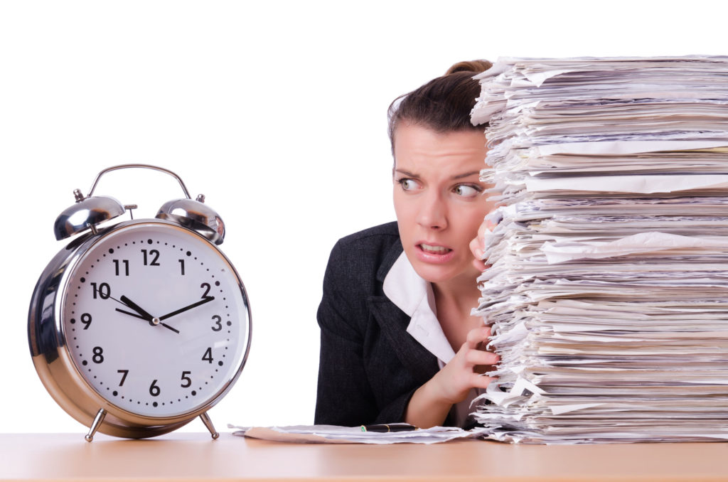 businesswoman under stress staring at clock from behind stack of papers