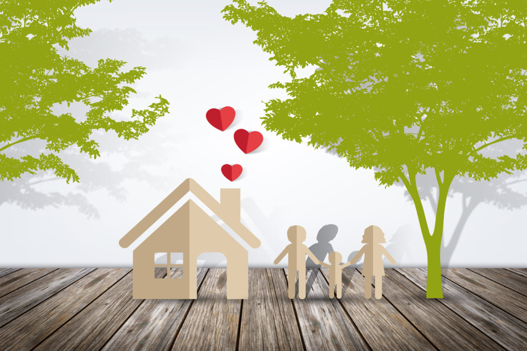Paper cutout of family, a house with hearts coming from a chimney and trees in the background